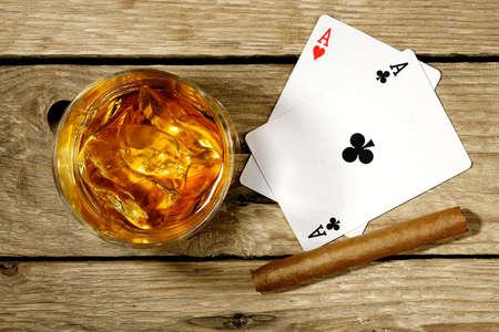 cigarro: whisky con las cartas y los cigarros en superficie de madera vieja
