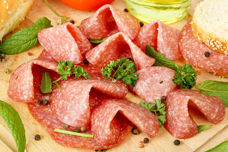 salami slices: sausage salami slices with other food ingredients on wooden surface