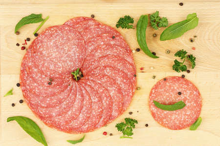salami slices: sausage salami slices with parsley and mint on wooden surface Stock Photo
