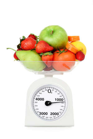 kilos: scale with fruits and vegetables isolated on white, healthy diet concept Stock Photo