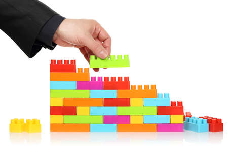 vision repair: businessman adding toy block to a wall, abstract concept Stock Photo