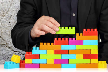 adding: businessman adding toy block to a wall, abstract concept Stock Photo