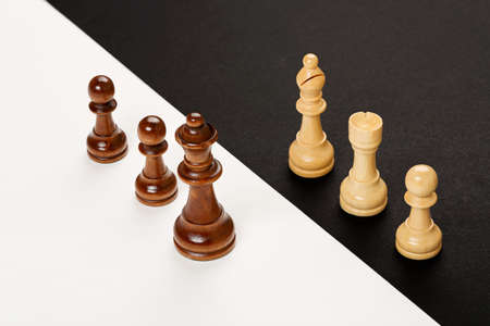 contrast: wooden chess pieces on black and white background, abstract concept Stock Photo