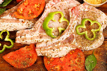 pork chops: raw pork chops with other ingredients on wood Stock Photo
