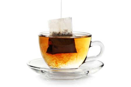 分離された茶の透明カップにティーバッグ