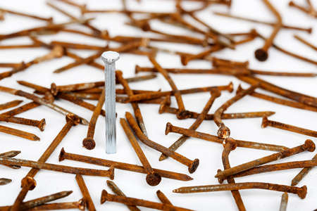 new steel nail standing among rusty ones, abstract concept Stock Photo