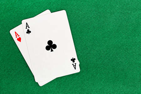 games hand: blackjack with two aces on green felt texture