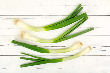 spring onions: green onions or scallions on white wooden planks
