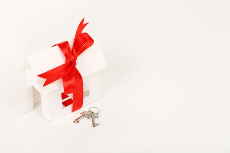home loan: white cardboard house with ribbon and keys on white surface Stock Photo