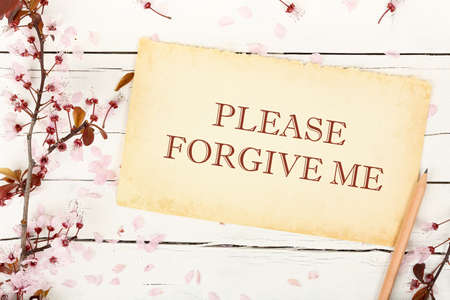 forgive me on paper with almond tree twig on white wood Stockfoto