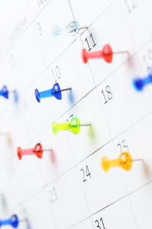 colorful pushpins on white calendar clsoe up, shallow dof