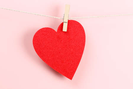 red felt heart caught on clothesline with peg against pink background Stock Photo