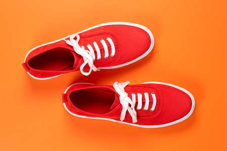 pair of red suede shoes on orange surface Stock Photo