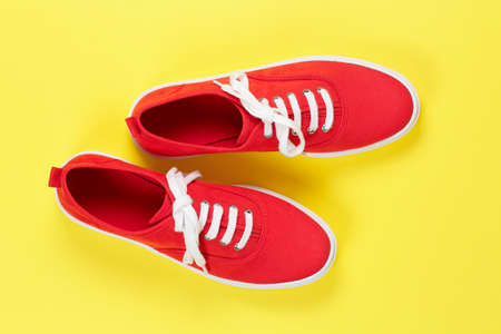 pair of red suede shoes on yellow surface Stock Photo