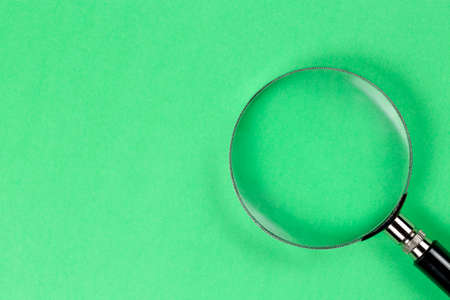 closeup of magnifying glass on green paper Imagens