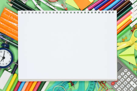 blank spiral notebook on large variety of school supplies