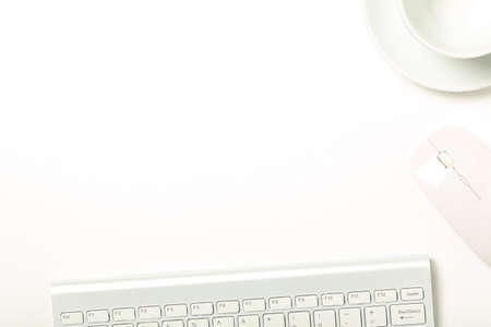 keyboard, mouse and cup on white office desk with copy space