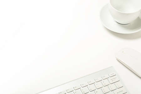 keyboard, mouse and empty cup on white office desk with copy space