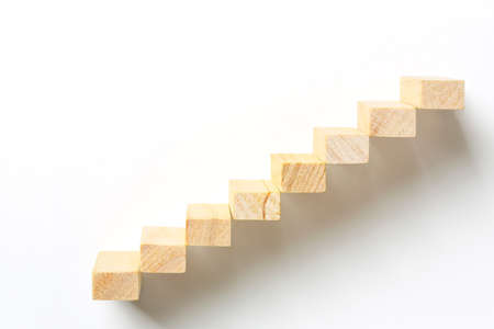 wooden toy blocks as staircase on white, abstract concept