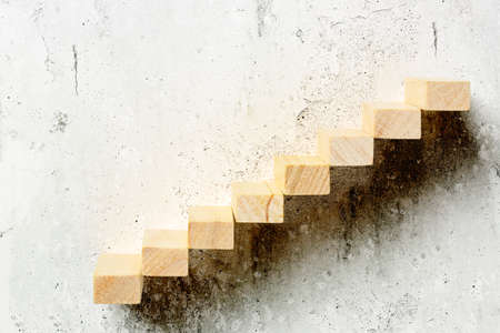 wooden toy blocks as staircase on old wall, abstract concept Stockfoto