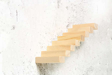wooden toy blocks as staircase on grungy wall, abstract concept
