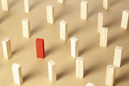 red wooden block among unpainted ones, concept for leadership or being different