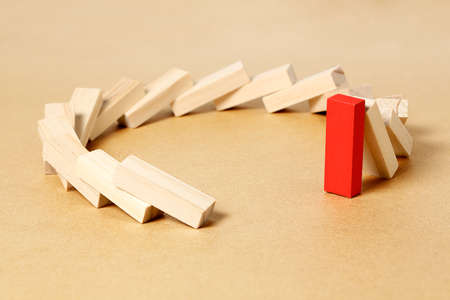 red toy block refusing to fall, abstract leadership or different concept