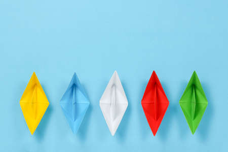 colorful paper boats on blue surface, abstract concept Stockfoto