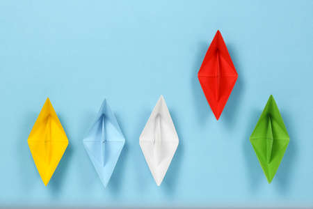 colorful paper boats on blue surface, red is leading, abstract concept