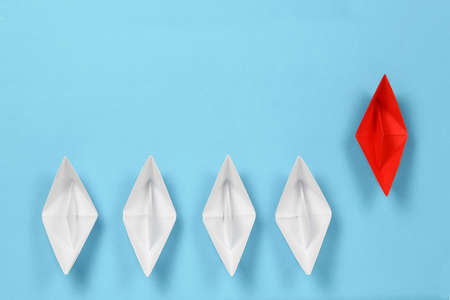 red paper boat leading the race against white paper boats, abstract concept Stockfoto