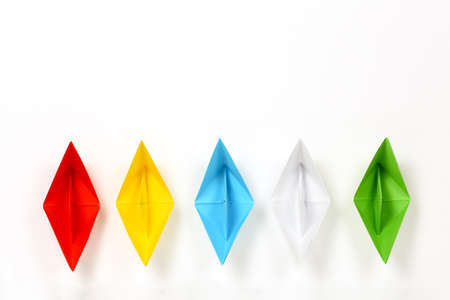colorful paper boats on white, abstract concept