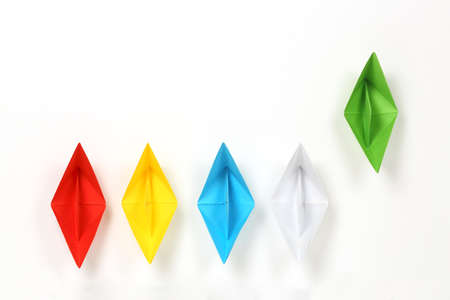 colorful paper boats on white, green boat is leading, abstract concept