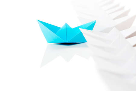 blue paper boat leading the race against white ones Imagens