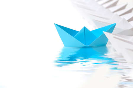 blue paper boat leading the race against white ones Stockfoto