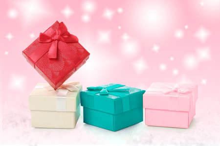 colorful gift boxes with ribbon against abstract pink background