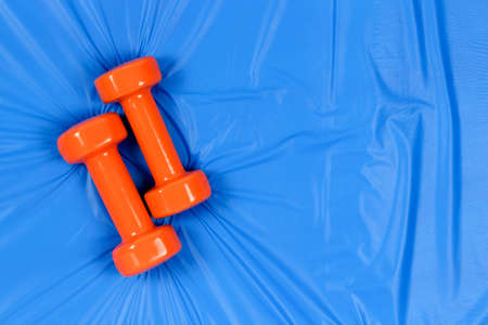 orange dumbbells on blue mat with copy  space