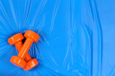 orange dumbbells and water on blue mat with copy  space