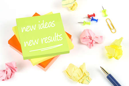 new ideas new results written on adhesive notes with crumpled paper and pen on white Imagens