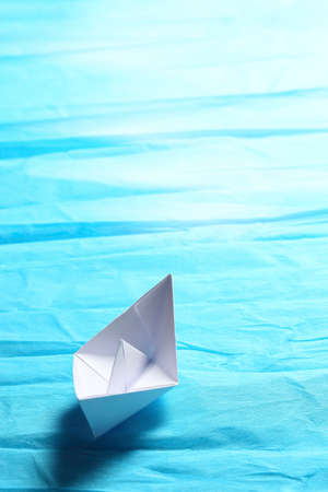 white paper boat sailing on cyan surface, hope in the horizon Archivio Fotografico