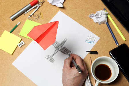 red paper plane flying over office desk, sketch of plane underneath, creativity concept Stock Photo