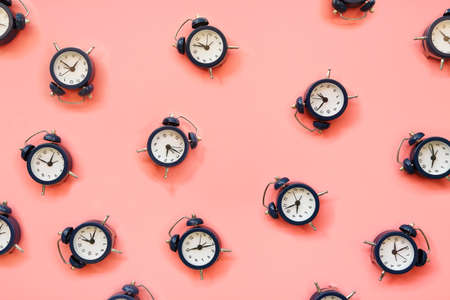 number of alarm with different time on pink surface Zdjęcie Seryjne