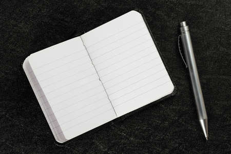 open and blank agenda book with pen on black surface Zdjęcie Seryjne