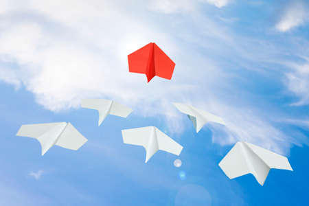 red paper plane leading others in bright sky, leadership concept Zdjęcie Seryjne