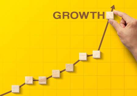 Wooden blocks arranged in an increasing graph with the word GROWTH on yellow background. Business growth, career growth or growth concept. Foto de archivo