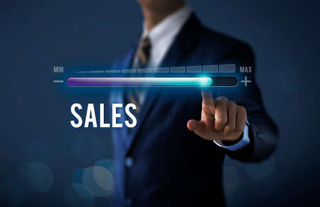 Sales growth, increase sales or business growth concept. Businessman is pulling up progress bar with the word SALES on dark tone background. Reklamní fotografie