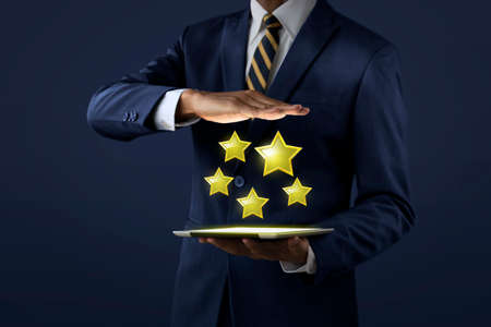 Increase rating, ranking, review, evaluation or classification concept. Businessman is showing five stars rating that projected from tablet on dark tone background. Standard-Bild