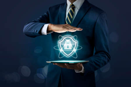Cyber security, internet security or information protection service concept. Businessman is showing cyber security icon which projected from tablet on dark tone background.