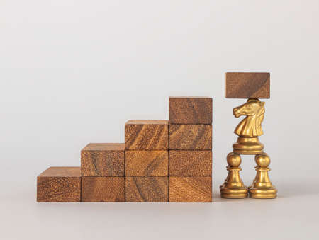 Teamwork to success in business or cooperation to success concept. Chess are cooperating to lift the next wooden piece in front of the wooden stacked staircase.