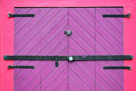 Closed purple door entrance at red wall photo