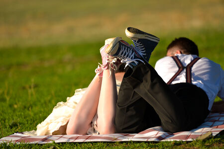 Kiss of bride and groom lying in grass